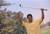 Hispanic man cheering with golf club — Stock Photo