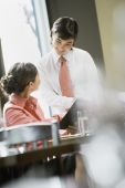Asian woman ordering in restaurant — Stock Photo