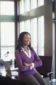 African businesswoman sitting on edge of desk — Stock Photo