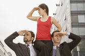 Hispanic businesswoman sitting on co-worker's shoulders — Stock Photo