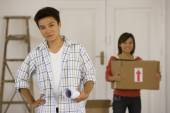 Asian couple with blueprints in new house — Stock Photo