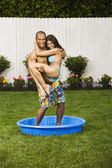 Multi-ethnic couple standing in kiddie pool — Stock Photo