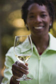 African woman holding up wine glass — Stock Photo