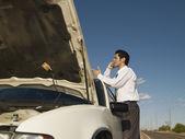 Hispanic man broken down on side of road — Stock Photo