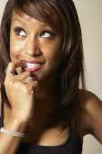 African American woman biting finger — Stock Photo