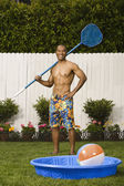 Mixed Race man holding net next to kiddie pool — Stock Photo