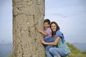 Mother and son hugging column — Stock Photo