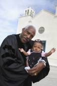 African American Reverend holding baby — Stock Photo