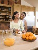 Multi-ethnic couple making orange juice — Stock Photo