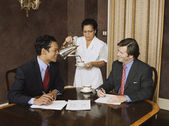 Hispanic maid pouring coffee for businessmen — Foto de Stock