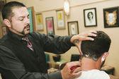 Hispanic barber shaving man's neck — Stock Photo