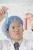 Asian male scientist comparing vials — Stock Photo