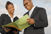 African businesspeople reading paperwork — Stock Photo
