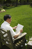 Senior Asian man reading in backyard — Stock Photo