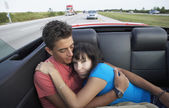 Multi-ethnic couple in back of convertible — Stock Photo