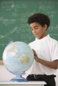 Hispanic boy looking at classroom globe — Stock Photo