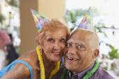 Multi-ethnic senior couple wearing party hats — Stock Photo