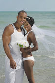 African bride and groom hugging at beach — Stock Photo