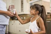 Hispanic girl handing medication to pregnant mother — Stock Photo