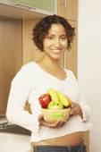 Woman holding bowl of fruit — Foto de Stock