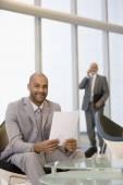 African businessman holding paperwork — Stock Photo