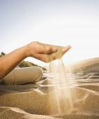 Pacific Islander man spilling sand out of hand — Stock Photo