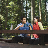 Indian couple drinking coffee in woods — Stock Photo