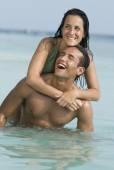 Hispanic couple playing in water — Foto Stock