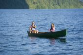 Asian mother and daughter rowing in canoe — Stock Photo