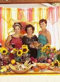 Mother and daughters behind buffet table — Stock Photo