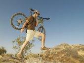 Hispanic man carrying bicycle — Stock Photo