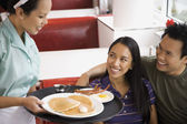 Asian couple being served food at diner — Stock Photo