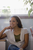African American woman sitting indoors — Stockfoto