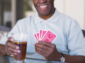 Senior African man playing cards — Stock Photo