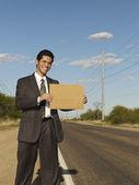 Hispanic businessman holding blank sign — Stock Photo