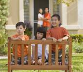Asian siblings sitting in bench — Stock Photo