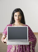 Indian woman holding laptop — Stock Photo