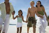 Família hispânica de mãos dadas na praia — Fotografia Stock