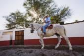 Hispanic man riding horse — Stock Photo