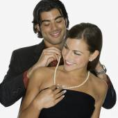 Mixed Race man fastening girlfriend's necklace — Stock Photo