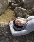Hispanic woman laying on rock formation — Stock Photo