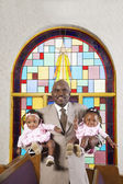 African American father holding babies in church — Stock Photo