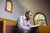 African American man reading Bible in church — Stock Photo