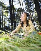 Asian girl listening to headphones — Stock Photo