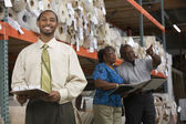 African American sales representative in carpet warehouse — Stock Photo
