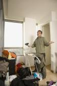 Man shrugging shoulders in messy room — Stock Photo