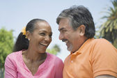 Multi-ethnic couple smiling at each other — Stock Photo