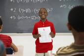 Boy holding paper in front of class — Stock Photo