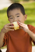 Asian boy eating apple — Stockfoto