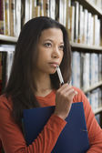 Mixed race woman thinking in library — Stock Photo